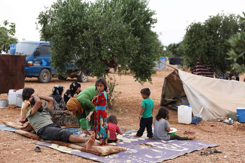 Syrians who fled shelling by regime forces and their allies in the Jihadist-held Idlib province, rest in an olive grove where displaced families took refuge, near the village of Aqrabat, in the Harem district of the same province on the border with Turkey on May 31, 2019.    / AFP / Nazeer Al-khatib