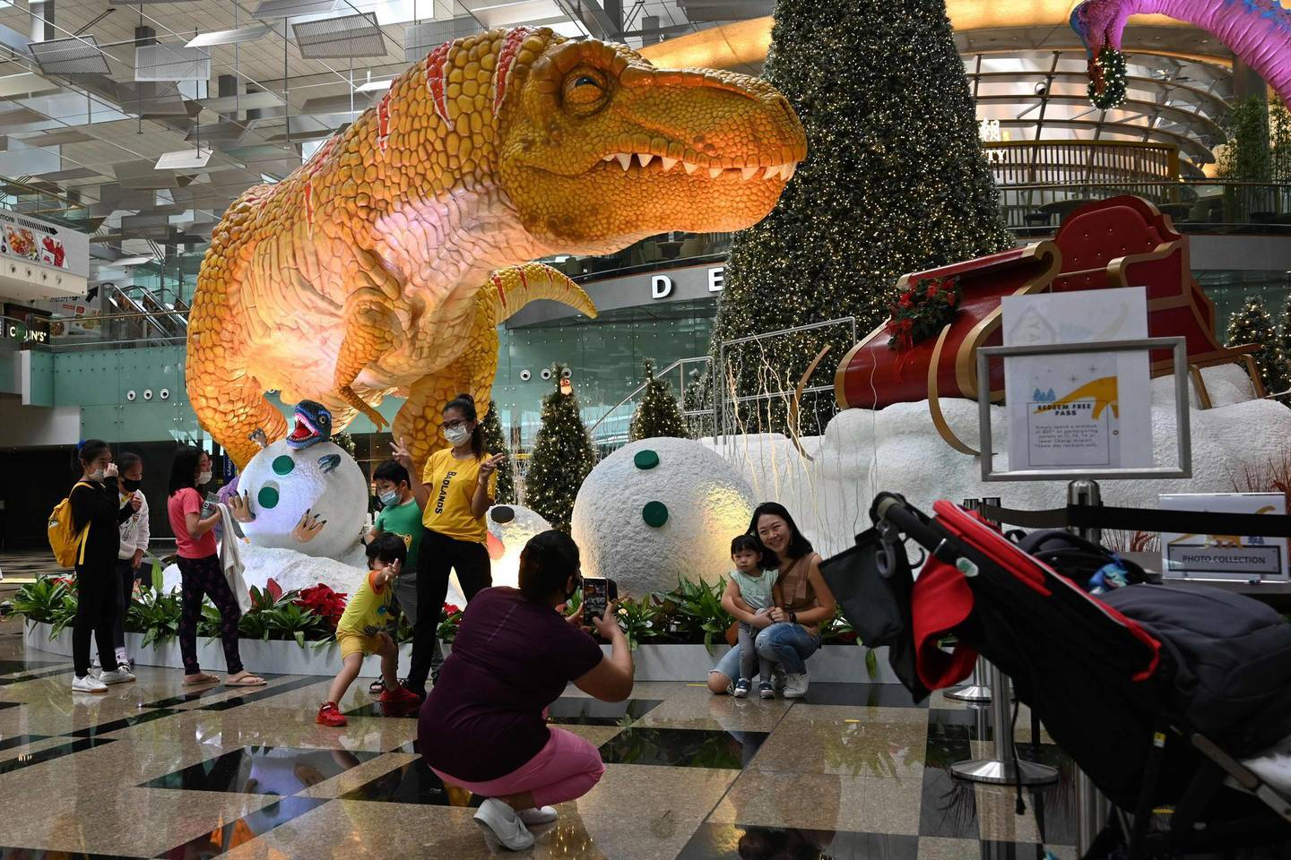 Visitors take photographs with their children in front of the Christmas decorations at a terminal of the Changi International Airport in Singapore on December 7, 2020.  / AFP / Roslan RAHMAN
