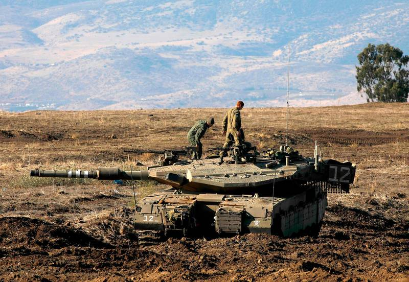 """TOPSHOT - Israeli soldiers and armoured vehicles are pictured on November 19, 2019 near the border with Syria in the annexed Golan Heights. Israel's anti-missile defence system intercepted four rockets fired from neighbouring Syria on Tuesday, the army said. """"Four launches were identified from Syria towards Israeli territory which were intercepted by the Israeli air defense systems,"""" the Israeli army said in a statement.  / AFP / JALAA MAREY"""