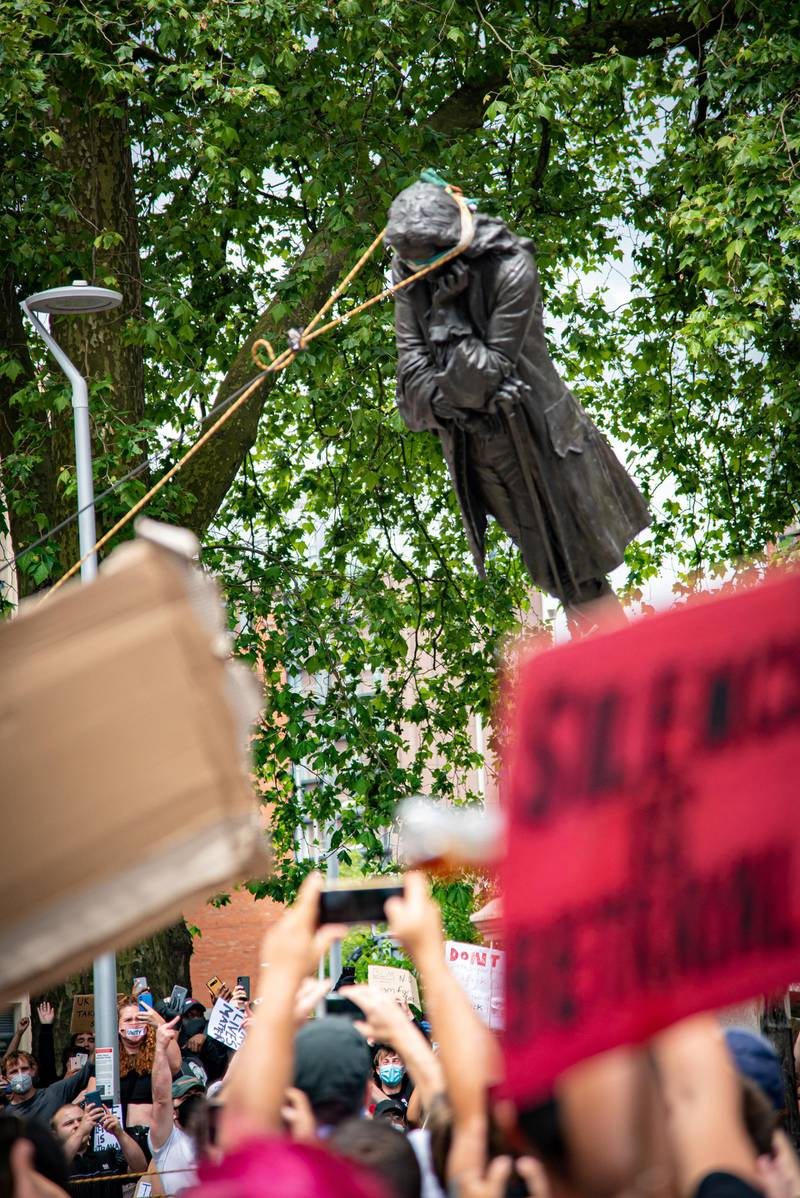 The statue of Edward Colston falls down as protesters pull it down, following the death of George Floyd who died in police custody in Minneapolis, in Bristol, Britain, June 7, 2020. Picture taken June 7, 2020. Keir Gravil/via REUTERS THIS IMAGE HAS BEEN SUPPLIED BY A THIRD PARTY. MANDATORY CREDIT.