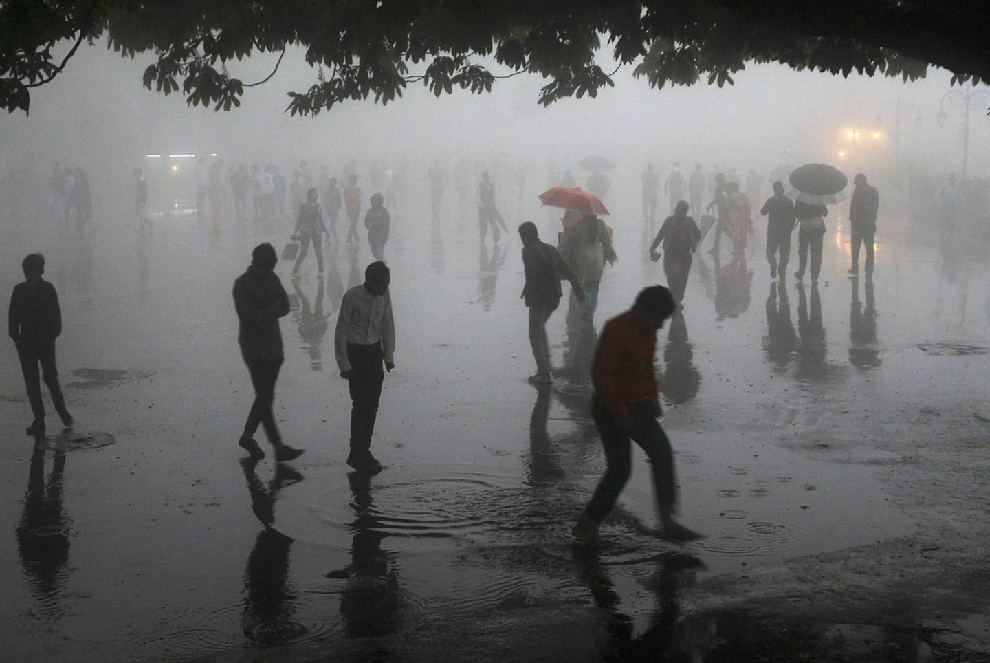 TOPSHOT - This photo taken on May 2, 2018 shows people walking under heavy rainfall in the northern hill town of Shimla in Himachal Pradesh state. Dust storms tore across northern India killing at least 77 people and injuring 143 as trees and walls were flattened by powerful winds, officials said May 3.   / AFP PHOTO / -
