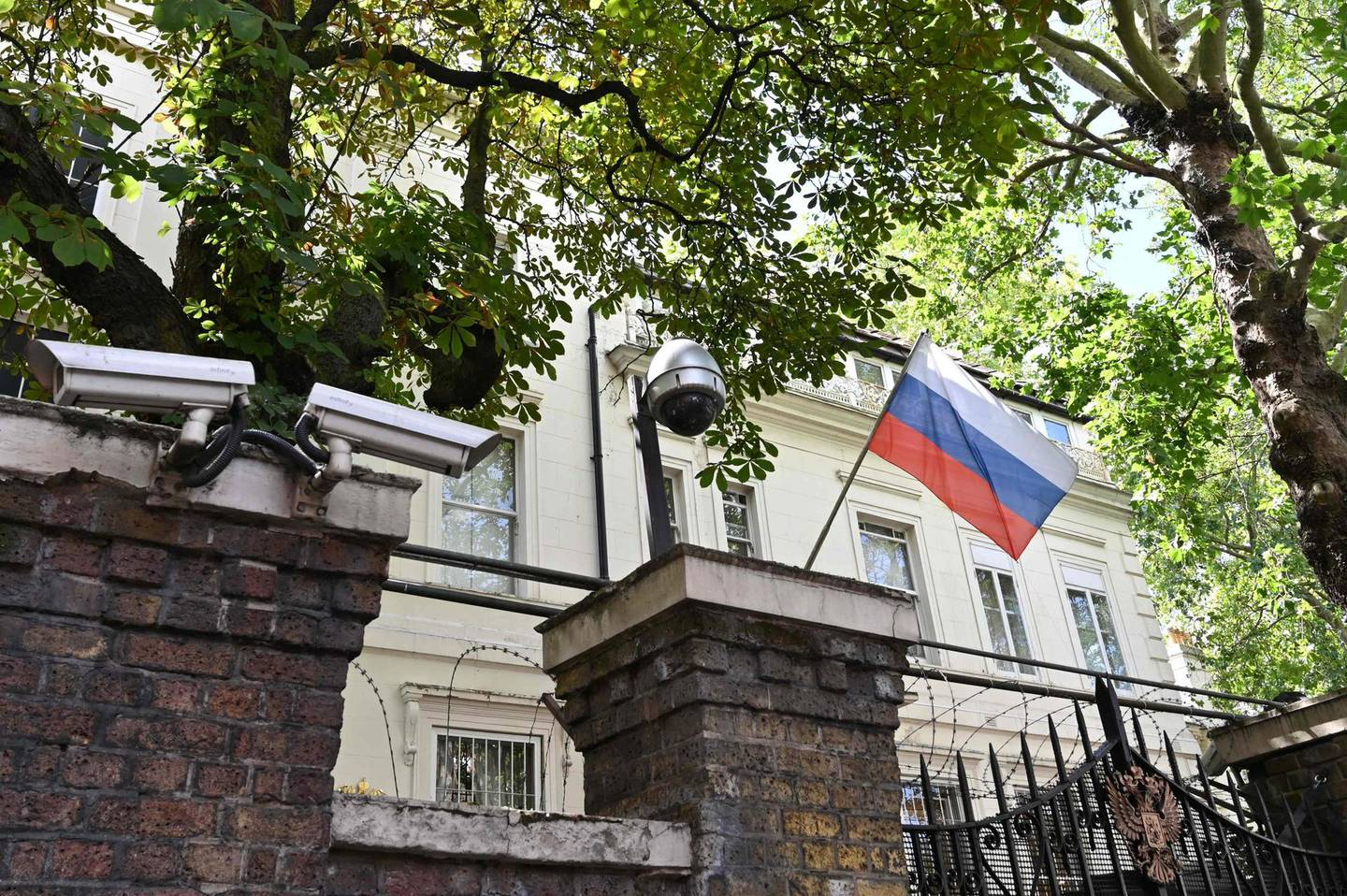 """(FILES) In this file photo taken on July 21, 2020 A Russian flag flies by surveillance cameras at the entrance to the Russian consulate in London.  Russia's ambassador to Britain said on March 21, 2021 that diplomatic ties between the two countries were """"nearly dead"""", after a UK strategic review this week branded Moscow an """"acute direct threat"""". Andrei Kelin also criticised Britain's decision to bolster its nuclear stockpile, arguing the reversal of decades of policy was a violation of various international agreements.  / AFP / JUSTIN TALLIS"""