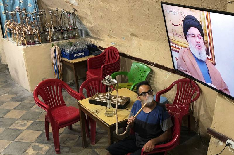 A man smokes a hookah as he watches Lebanon's Hezbollah leader Sayyed Hassan Nasrallah speak on television inside a coffee shop in the port city of Sidon, Lebanon July 12, 2019. REUTERS/Ali Hashisho