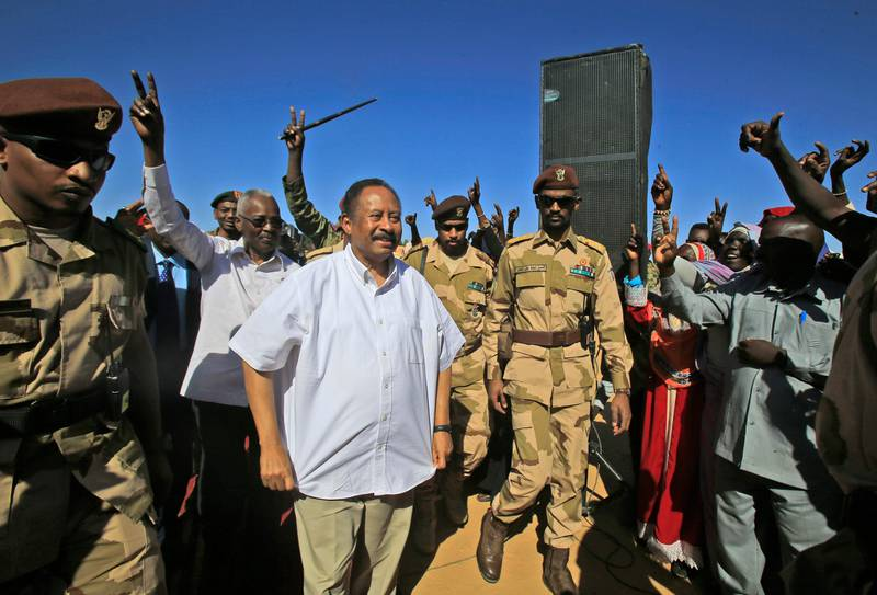 Sudan's Prime Minister Abdalla Hamdok (C) is greeted by supporters upon arriving in El-Fasher, the capital of the North Darfur state, on November 04, 2019. Hamdok's one-day visit was his first as prime minister to the devastated region, where a conflict that erupted in 2003 has left hundreds of thousands dead and millions displaced. He said his government was working toward bringing peace to war-torn Darfur as he met hundreds of victims of the conflict who demanded swift justice. / AFP / ASHRAF SHAZLY