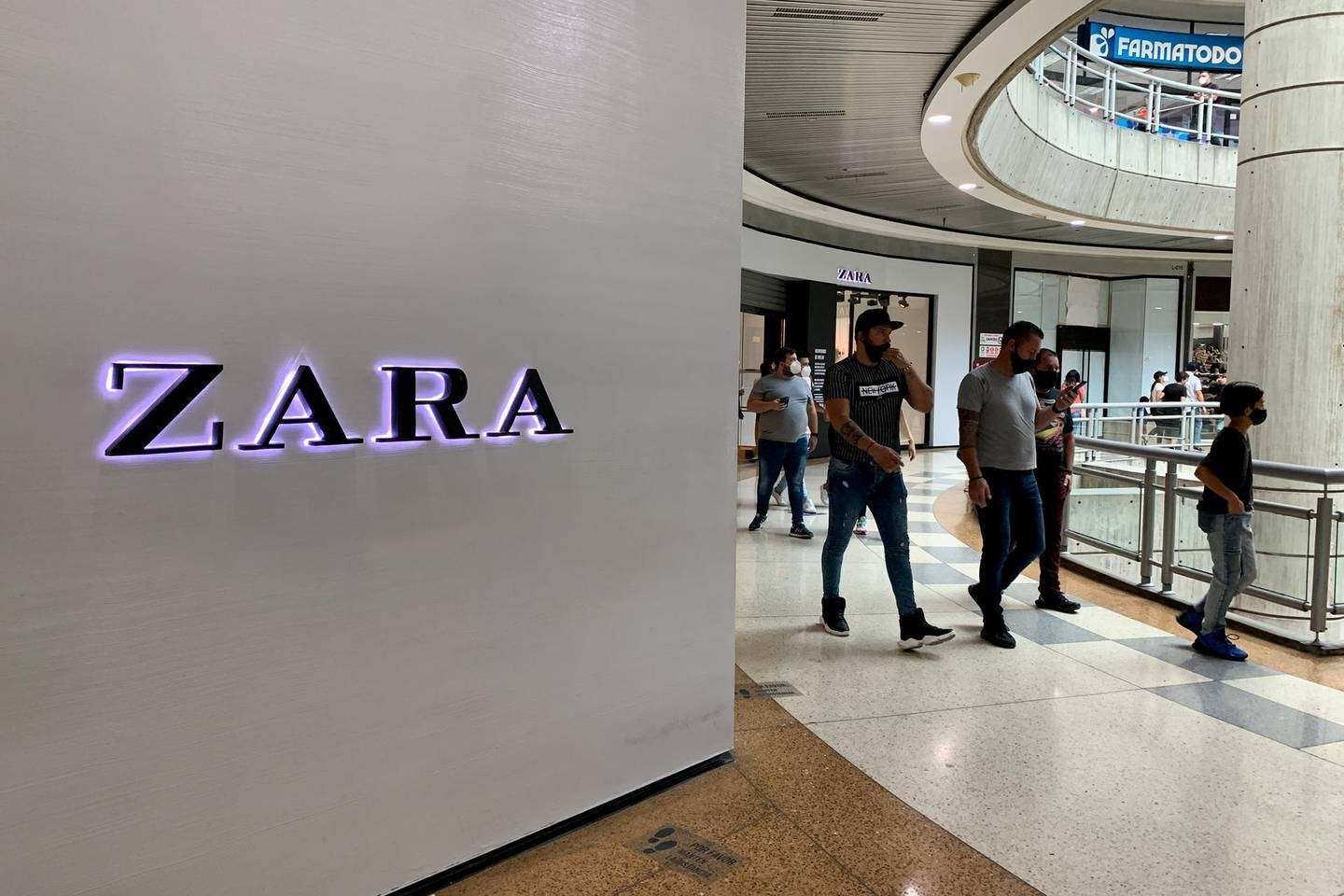 Shoppers walk past a Zara store at Sambil Shopping Center in Caracas, Venezuela, on Saturday, May 22, 2021. The franchise operator of Zara and two other popular apparel chains will close all of its stores in Venezuela in the next few weeks. Photographer: Manaure Quintero/Bloomberg