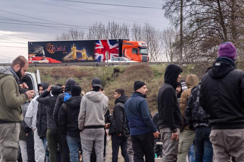 Migrants queue for hot-meals from the Salam Charity aid agency food truck as a Belgian Welsi B.V. haulage truck decorated with a British Union flag, also known as a Union Jack, passes along a highway in Dunkirk, France, on Thursday, Dec. 19, 2019. In January, British and French authorities agreed to a joint action plan that includes spending more than 6 million pounds ($7.8 million) for additional measures to deter migrants. Photographer: Geert Vanden Wijngaert/Bloomberg