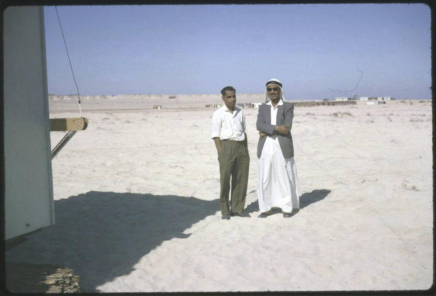 Jebel Dhana, Abu Dhabi 1963 Two employees of the British Bank of the Middle East, Abu Dhabi taken on a construction site in Jebel Dhana, where Wimpeys were building a new oil terminal. On the left is, Juveira , a clerk and on the right, Ali Bhutti, who was a cashier and an Abu Dhabi local. [Note - at this time there were very few locals, who had had an education and it was certainly not common to find many who spoke English. Shortly after this photograph was taken, Bhutti was summoned to the Palace by the Ruler, Sheikh Shakbhut and appointed the new Postmaster of Abu Dhabi. The Ruler had decided that he would take over the running of the Postal Administration from the British Goverment. Although Bhutti enjoyed his work with the Bank and his prospects with them were good in those days you did not refuse the wishes of the Ruler!] Photo by David Riley