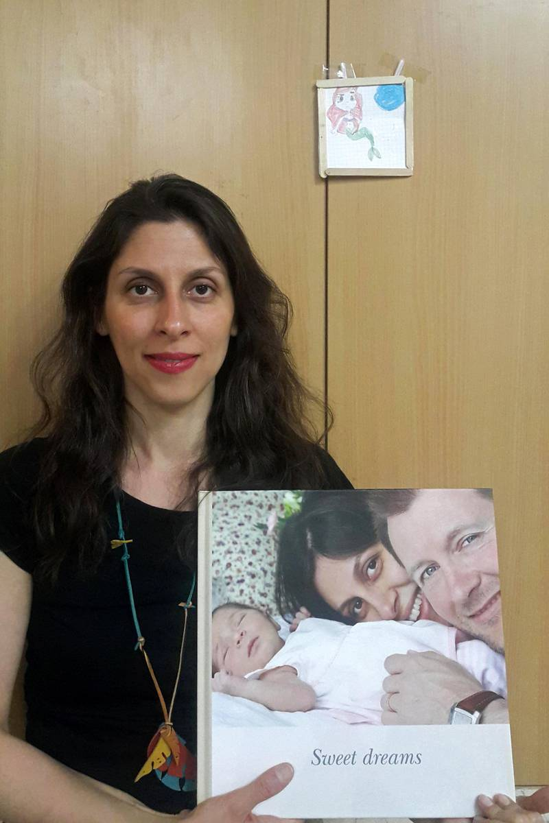 """A handout picture released by the Free Nazanin campaign on March 17, 2020 shows Nazanin Zaghari-Ratcliffe holding an old picture of herself with her husband and daughter as she poses for a photograph in West Tehran, Iran following her release from prison for two weeks. - Nazanin Zaghari-Ratcliffe, a British-Iranian woman serving a five-year prison term in Tehran for sedition, was released from jail for two weeks on Tuesday, March 17, her husband said. (Photo by - / Free Nazanin campaign / AFP) / RESTRICTED TO EDITORIAL USE - MANDATORY CREDIT """"AFP PHOTO / FREE NAZANIN CAMPAIGN"""" - NO MARKETING NO ADVERTISING CAMPAIGNS - DISTRIBUTED AS A SERVICE TO CLIENTS"""
