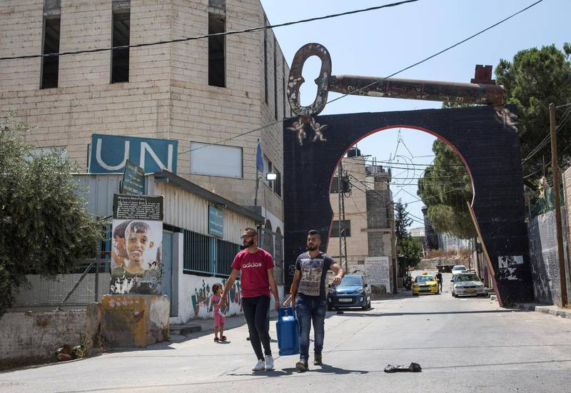 Palestinians carry cooking gain the entrance of the Aida refugee camp near the city of Bethlehem on June 23,2019.Photo by Heidi Levine for The National
