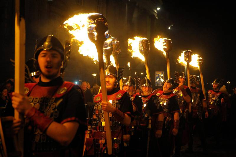 Members of the Up Helly AA Vikings from Shetland prepare to lead the torchlight procession through the streets of Edinburgh in Scotland on December 30, 2016, as the city begins to celebrate Hogmanay - The procession is the opening event of Edinburgh's Hogmanay 2016/17. Over 40,000 people are expected to throng the streets of the capital to watch the torch carriers as they illuminate the city, culminating in a breath-taking fireworks finale. (Photo by ANDY BUCHANAN / AFP)