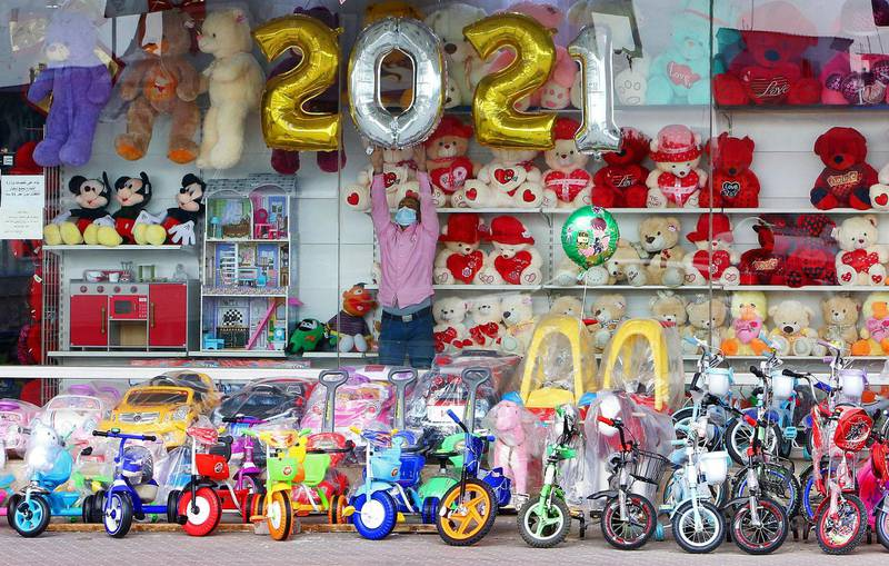 A vendor decorates his toy store ahead of the New Year in Kuwait City on December 31, 2020. / AFP / YASSER AL-ZAYYAT