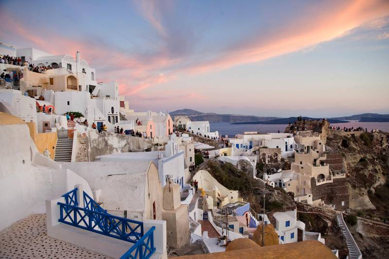 Tourists watching the sunset in Oia, pronounced 'Ia', it is the most famous of all villages of Santorini. It is world known for its quite life and fantastic sunset and it is obviously the most beautiful and picturesque village of Santorini. (Photo by In Pictures Ltd./Corbis via Getty Images)