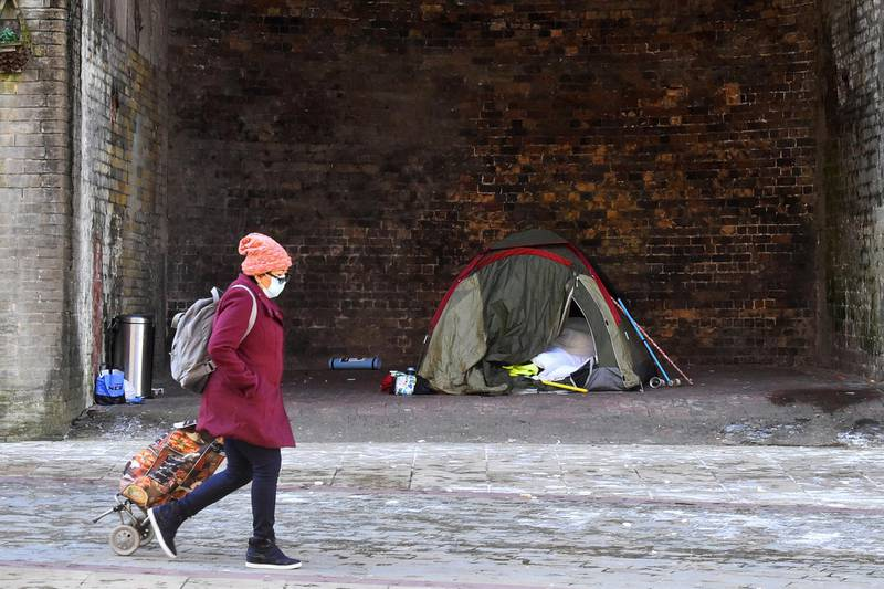 BRADFORD-ENGLAND - FEBRUARY 12: A woman wearing a mask walks past a homeless tent in Bradford City Center on February 12, 2021 in Bradford, England. (Photo by Nathan Stirk/Getty Images)