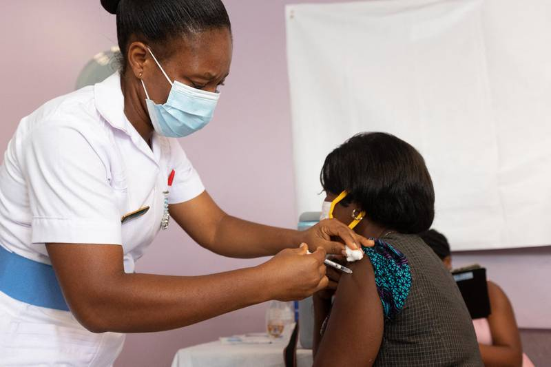 A woman receives an Oxford/AstraZeneca vaccine at the Ridge Hospital in Accra, Ghana on March 2, 2021. (Photo by Nipah Dennis / AFP)