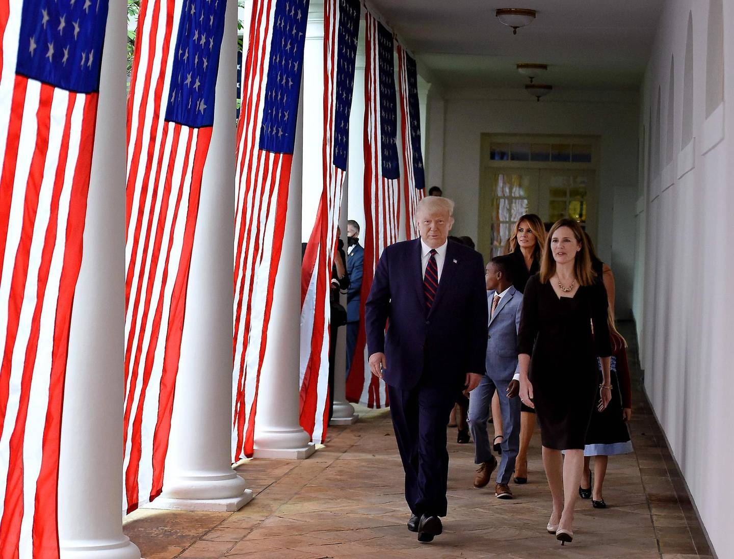 US President Donald Trump (L) and Judge Amy Coney Barrett (R), with US First Lady Melania Trump, arrive at the Rose Garden of the White House in Washington, DC, on September 26, 2020. Judge Amy Coney Barrett, who was nominated Saturday to the US Supreme Court, is a darling of conservatives for her religious views but detractors warn her confirmation would shift the nation's top court firmly to the right. / AFP / Olivier DOULIERY