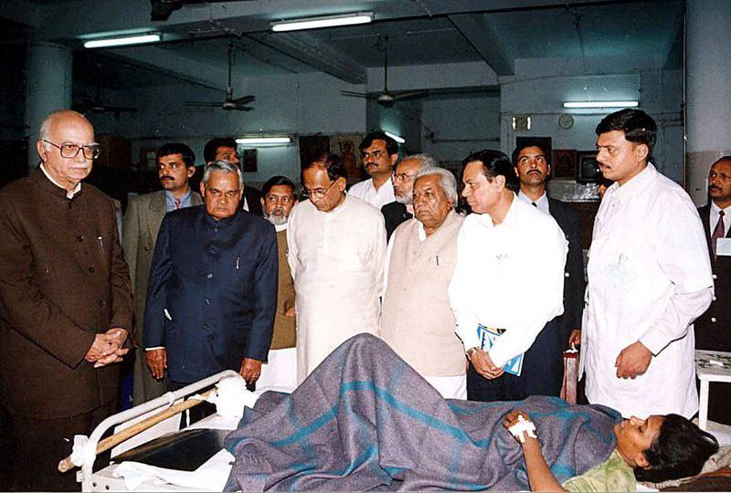 Indian home minister L.K.Advani (L) and Prime Minister Atal Behari Vajpayee (2nd/L) visit an injured earthquake victim at an army hospital in Bhuj, 29 January 2001. More than 20,000 people are feared dead in the worst disaster to hit India for five decades. AFP PHOTO STR (Photo by STR / AFP)