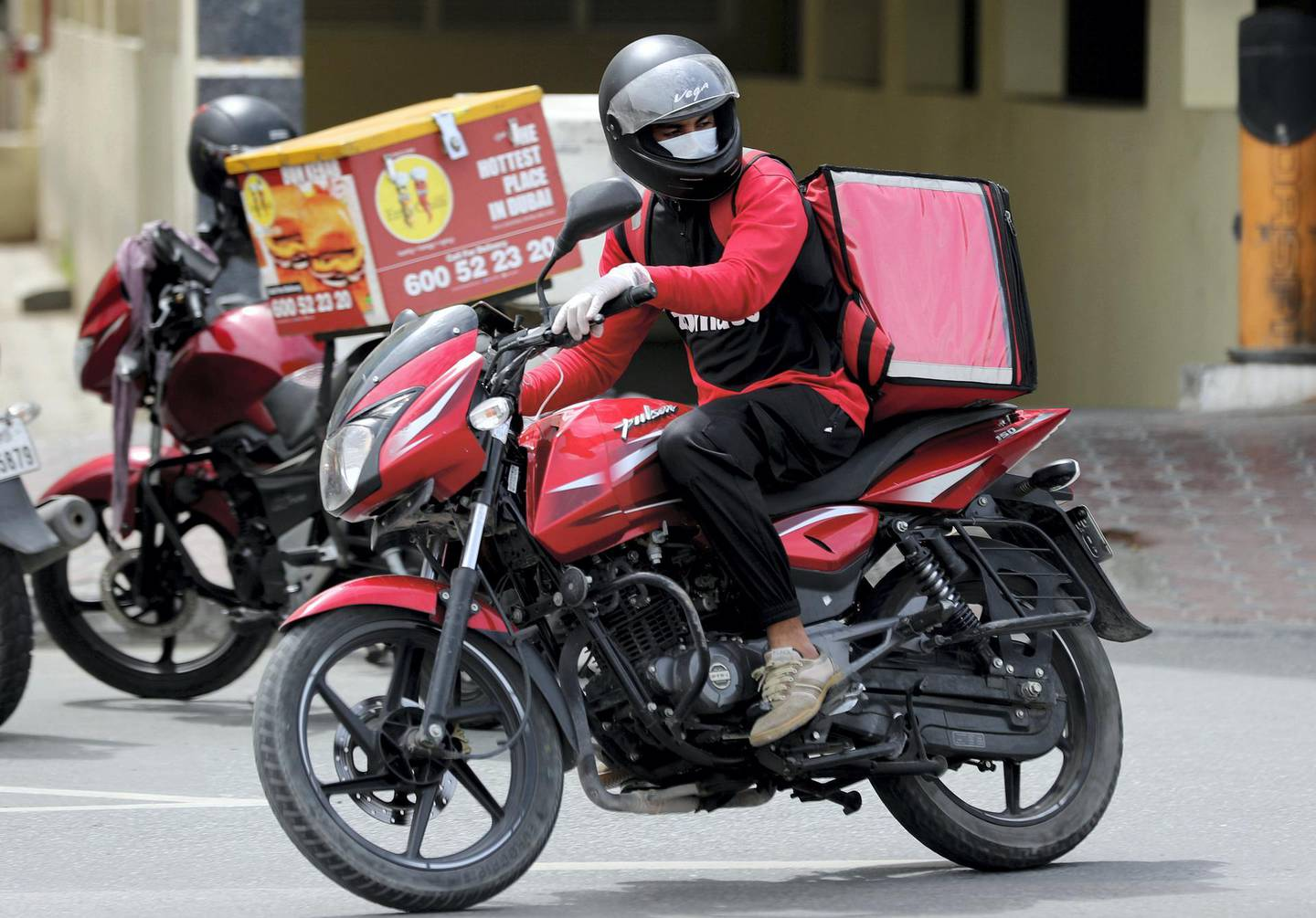 Dubai, United Arab Emirates - Reporter: N/A: A Zomato driver delivers food with a facemask on due to the corona outbreak. Monday, April 13th, 2020. Dubai. Chris Whiteoak / The National