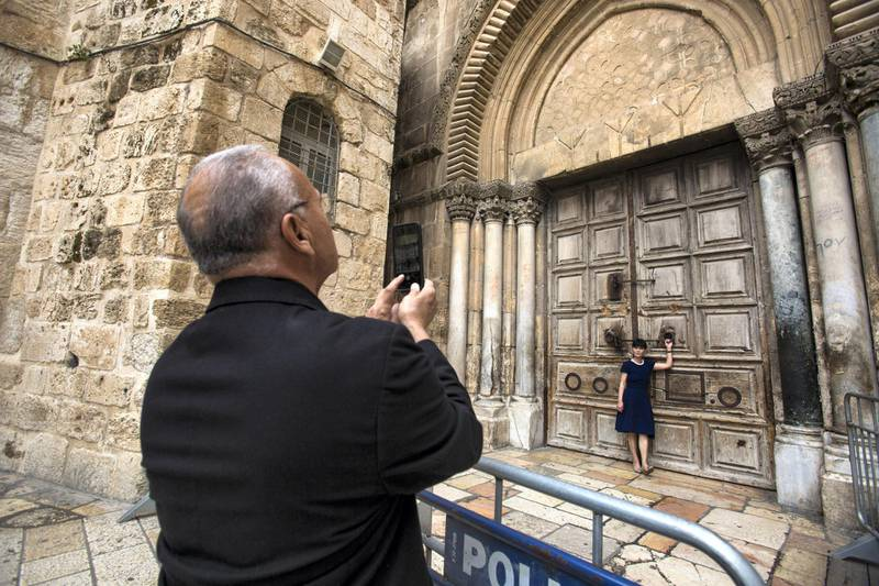 Christian pilgrims used the background for memorable photographs by the  giant closed wooden doors of the Church of the Holy Sepulchre in the Old City of Jerusalem on Monday February 26,2018.The Church of the Holy Sepulchre  remained closed for a second day after church leaders in Jerusalem closed it to protest against Israeli's announced plans by the cityÕs municipality earlier this month to collect property tax (arnona) from church-owned properties on which there are no houses of worship. (Photo by Heidi Levine for The National).