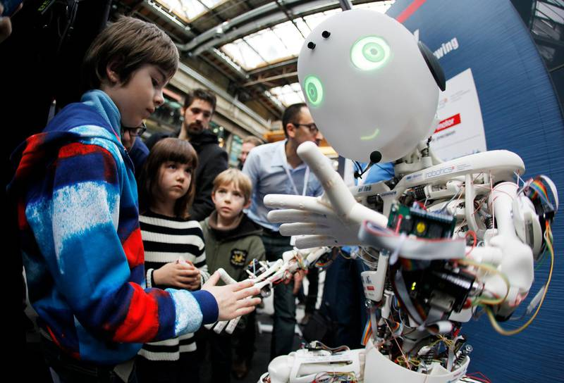 Children interact with the humanoid robot Roboy at the exhibition Robots on Tour in Zurich, March 9, 2013. A project team composed of scholars and industry representatives developed the prototype of the tendon driven humanoid robot Roboy within nine months.  Roboy was unveiled to the public today during the exhibition that is marking the 25th anniversary of the Artificial Intelligence Laboratory of the University of Zurich (AI Lab). Picture taken with fish-eye lens. REUTERS/Michael Buholzer (SWITZERLAND - Tags: SCIENCE TECHNOLOGY SOCIETY BUSINESS) - BM2E93916CJ01