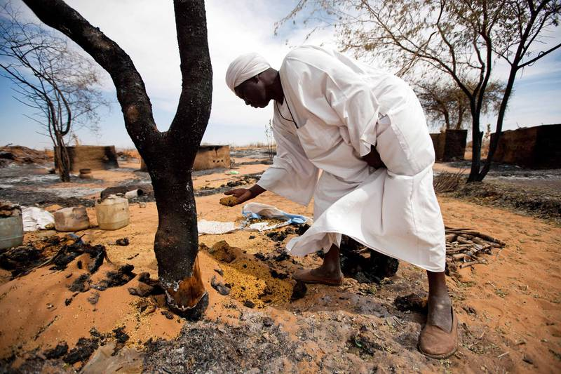 """A handout picture released by the United Nations-African Union Mission in Darfur (UNAMID) shows Sudanese Attahi Mohammed Sigit, the sheikh of Sigili village in North Darfur, showing to UNAMID peacekeepers damages in the village on November 6, 2012, days after an attack by a local militia during which his 18-year-old son was killed. Militia in Sudan's North Darfur state attacked the village and killed 13 people, a local source told AFP on November 3, adding to an upsurge of deadly violence in the area. AFP PHOTO/UNAMID/ALBERT GONZALEZ FARRAN == RESTRICTED TO EDITORIAL USE - MANDATORY CREDIT """"AFP PHOTO/UNAMID/ALBERT GONZALEZ FARRAN"""" - NO MARKETING NO ADVERTISING CAMPAIGNS - DISTRIBUTED AS A SERVICE TO CLIENTS == (Photo by ALBERT GONZALEZ FARRAN / UNAMID / AFP)"""