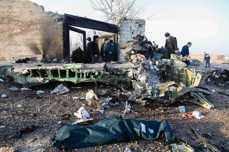 People stand near the wreckage after a Ukrainian plane carrying 176 passengers crashed near Imam Khomeini airport in Tehran on January 8, 2020. All 176 people on board a Ukrainian passenger plane were killed when it crashed shortly after taking off from Tehran on January 8, Iranian state media reported. State news agency IRNA said 167 passengers and nine crew members were on board the aircraft operated by Ukraine International Airlines. / AFP / ISNA / ISNA / ROHHOLLAH VADATI