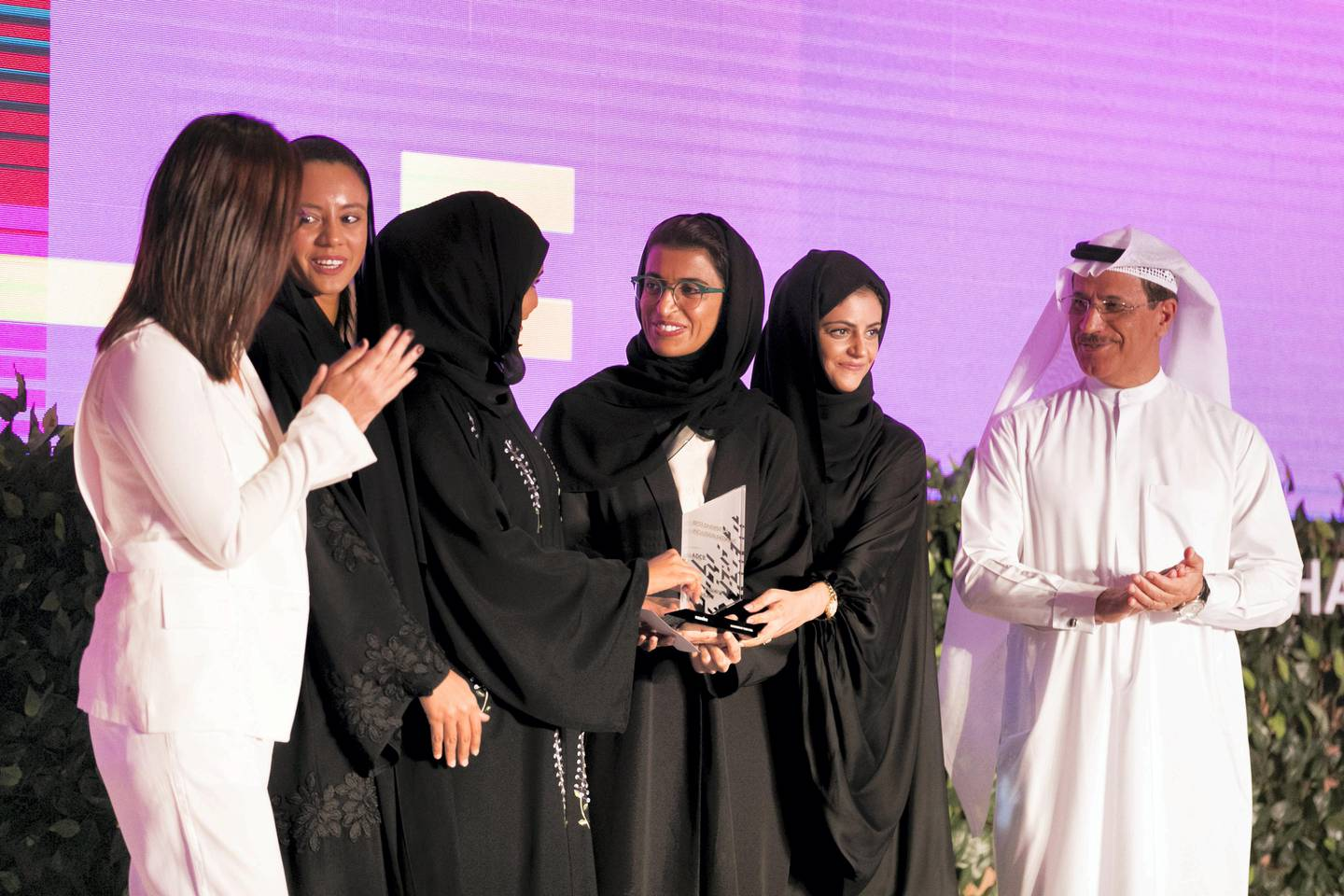 DUBAI, UNITED ARAB EMIRATES - OCT 25:  H.E. Sultan bin Saeed Al Mansouri, right, Ministry of Economy for the United Arab Emirates, and H.E. Noura Al Kaabi, second to right, Minister of State for Federal National Council Affairs, and Sophie Le Ray, left, CEO, Naseba  Founder, present the Best D&I Initiative award to ADCB at the Global WIL Economic Forum    Endorsed by the UAE Ministry of Economy for the past four years, Naseba Global WIL Economic Forum is bringing together up to 500 global business leaders, policy-makers, entrepreneurs, NGOs, artists and youth to champion diversity as the cornerstone of sustainable economic development.    (Photo by Reem Mohammed/The National)  Reporter: Suzanne Locke and Alice Haine Section: BZ