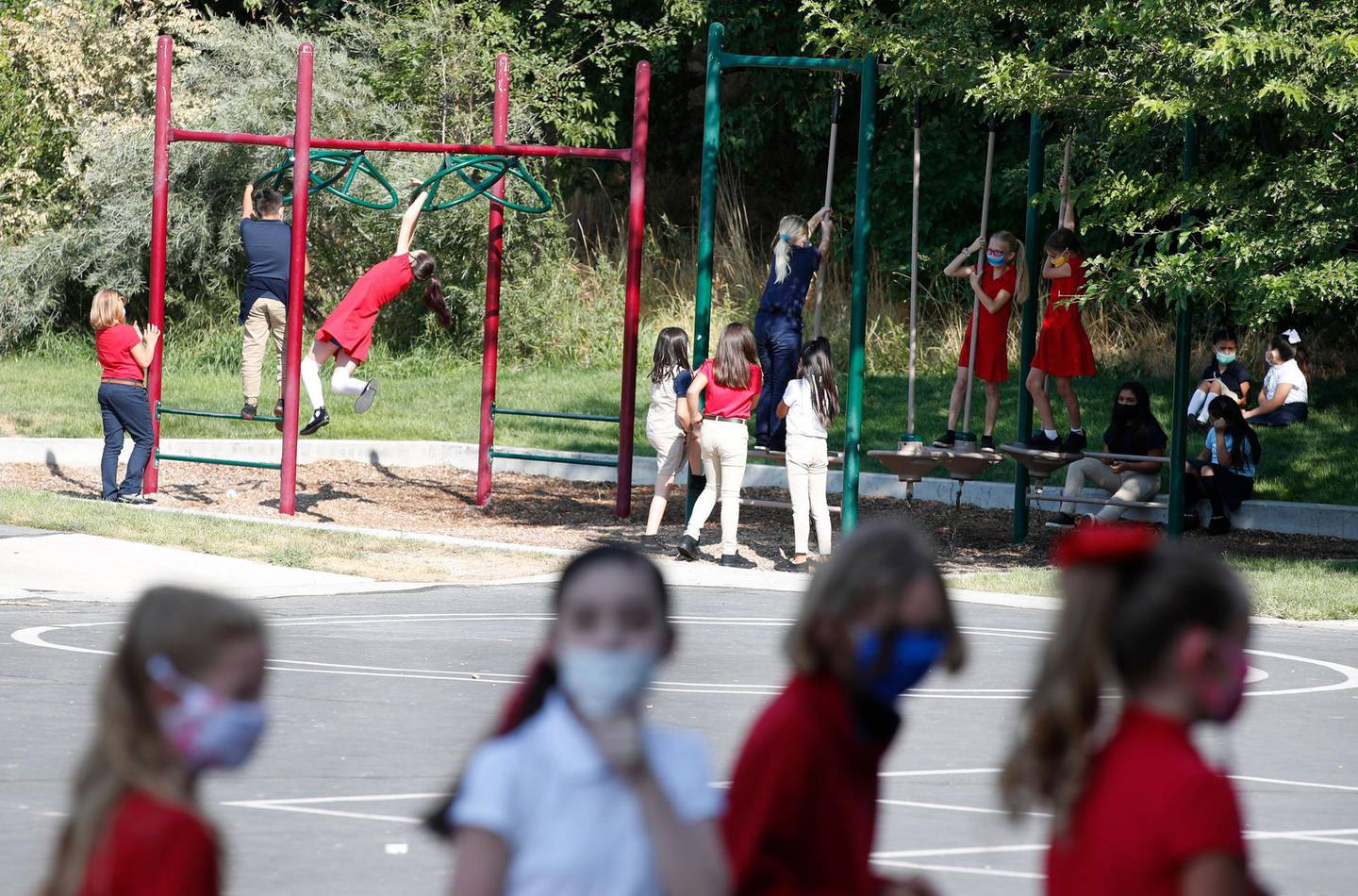 Students wearing protective masks play outside during recess at a public charter school in Provo, Utah, U.S., on Thursday, Aug. 20, 2020. Students and staff in Utah who don't wear a mask in K-12 schools in accordance with the  Governor Gary Herbert's mandate can be charged with a misdemeanor, reported the Salt Lake Tribune. George Frey/Bloomberg