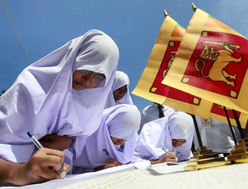 Muslim school girls sign a petition against a U.N. panel's report about Sri Lanka's war crimes, in Colombo April 21, 2011. The report to U.N. Secretary General Ban Ki-moon alleging tens of thousands of civilians were killed and war crimes committed at the end Sri Lanka's war in 2009 drew widespread political reaction this week from the Sri Lankan government. REUTERS/Dinuka Liyanawatte (SRI LANKA - Tags: POLITICS)