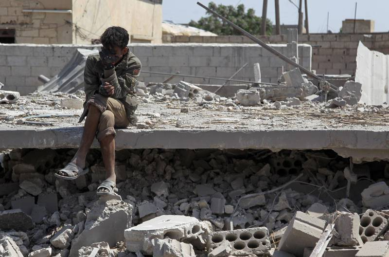 TOPSHOT - A man sits amidst the rubble of a building, destroyed during airstrikes by the Syrian regime and their allies near the town of Saraqeb in Syria's rebel-held northwestern province of Idlib on May 7, 2019.  Air strikes and shelling killed 13 civilians in northwestern Syria today, a monitor said, in the latest escalation to rattle a months-old truce and spark displacement. / AFP / Amer ALHAMWE