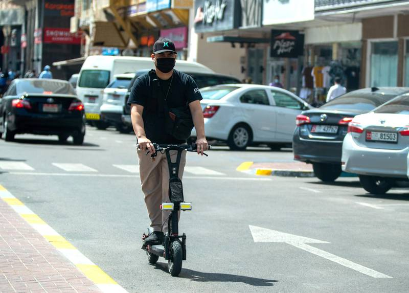 Abu Dhabi, United Arab Emirates, March 1, 2021.  An e-scooter rider counterflows oncoming traffic on Hamdan Steet, central Abu Dhabi.Victor Besa / The NationalSection:  NA