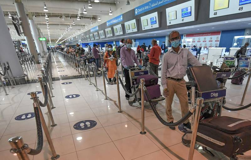 Indian nationals queue to check in at the Dubai International Airport before leaving the Gulf Emirate on a flight back to her country, on May 7, 2020, amid the novel coronavirus pandemic crisis.  The first wave of a massive exercise to bring home hundreds of thousands of Indians stuck abroad was under way today, with two flights preparing to leave from the United Arab Emirates. India banned all incoming international flights in late March as it imposed one of the world's strictest virus lockdowns, leaving vast numbers of workers and students stranded.           / AFP / Karim SAHIB