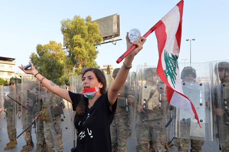 epa08665134 An anti-government protester carries a national flag as she shouts slogans in front of the Lebanese army soldiers during a protest on the road leading to the Presidential palace in Baabda, east Beirut, Lebanon, 12 September 2020. Hundreds of anti-government protesters gather outside the Presidential palace to protest against politicians, security and judicial officials, many of whom knew about the storage of the chemicals that exploded in Beirut's port on 04 August, and did nothing.  EPA/WAEL HAMZEH