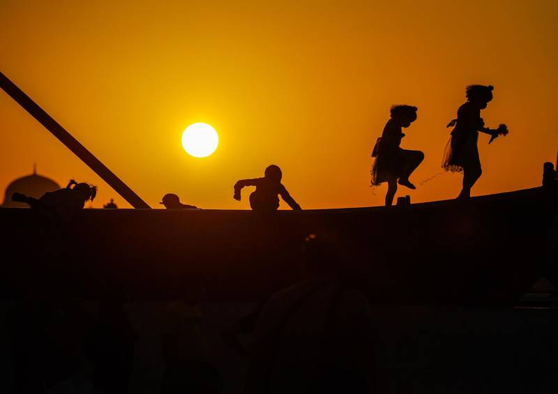 Abu Dhabi, United Arab Emirates, December, 2, 2020.   Abu Dhabi residents wait for the Al Fursan planes to arrive unfortunately the air display got cancelled.  Children play on top of a wooden fishing boat on display as the sun sets at the Corniche.Victor Besa/The NationalSection:  National News
