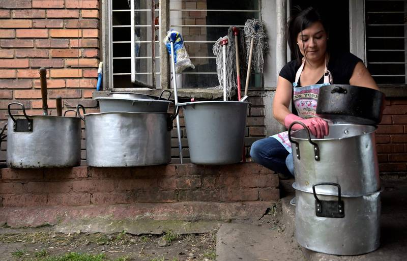 Maria Edilma Aguilar cleans pots as she works as a maid, in Bogota on February 14, 2021. Edilma lost her job in a beauty salon in March, 2020 due to the COVID-19 pandemic, and she had to work as a maid. / AFP / Raul ARBOLEDA