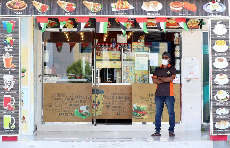 Umm Al Quwain, United Arab Emirates - Reporter: N/A: Corona. A waiter wears a facemask outside a food shop due to the Covid-19 outbreak. Saturday, April 18th, 2020. Umm Al Quwain. Chris Whiteoak / The National