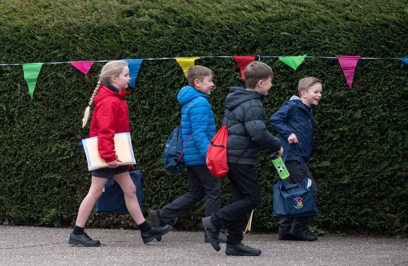 """Children arrive at a Primary Academy in Shipdham, England, Monday March 8, 2021. British children are returning to school on Monday after a two-month closure, part of what Prime Minister Boris Johnson said was a plan to get the country to """"start moving closer to a sense of normality."""" (Joe Giddens/PA via AP)"""