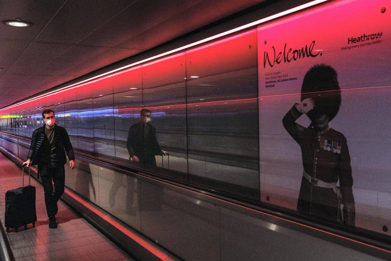 """LONDON, ENGLAND - JUNE 01: An airline passenger walks through an underpass between terminal buildings at Heathrow Airport on June 1, 2021 in London, England. Heathrow's Terminal 3 will now be reserved for direct arrivals from countries on the British government's """"red list,"""" from which travelers are subject to a 10-day hotel quarantine. Previously, there was concern about """"red list"""" arrivals queueing in Heathrow terminals alongside travelers from countries with a lower Covid-19 risk profile. (Photo by Chris J Ratcliffe/Getty Images)"""
