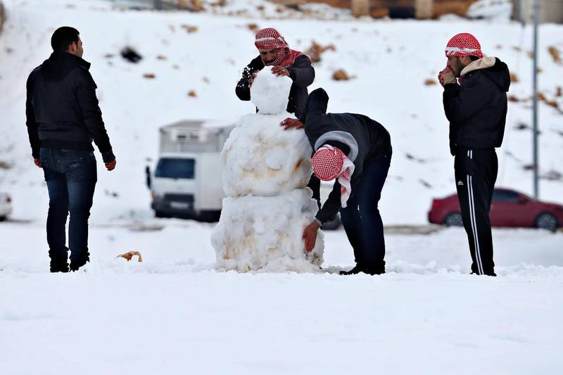 People play with snow after a heavy snowstorm in Amman January 11, 2015. A storm buffeted the Middle East with blizzards, rain and strong winds, keeping people at home across much of the region and raising concerns for Syrian refugees facing freezing temperatures in flimsy shelters. The storm is forecast to last several days, threatening further disruption in Lebanon, Syria, Turkey, Jordan, Israel, the West Bank and the Gaza Strip, which have all been affected. REUTERS/Muhammad Hamed (JORDAN - Tags: DISASTER ENVIRONMENT)