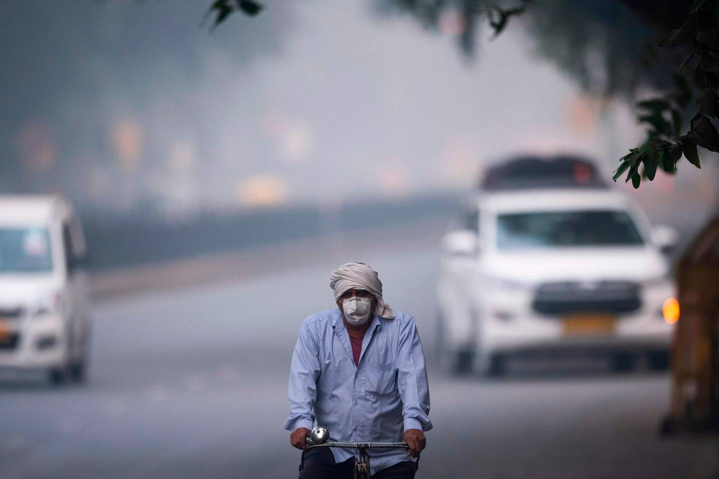 """A man wearing protective face mask rides a bicycle along a street in smoggy conditions in New Delhi on November 4, 2019. Millions of people in India's capital started the week on November 4 choking through """"eye-burning"""" smog, with schools closed, cars taken off the road and construction halted. / AFP / Jewel SAMAD"""