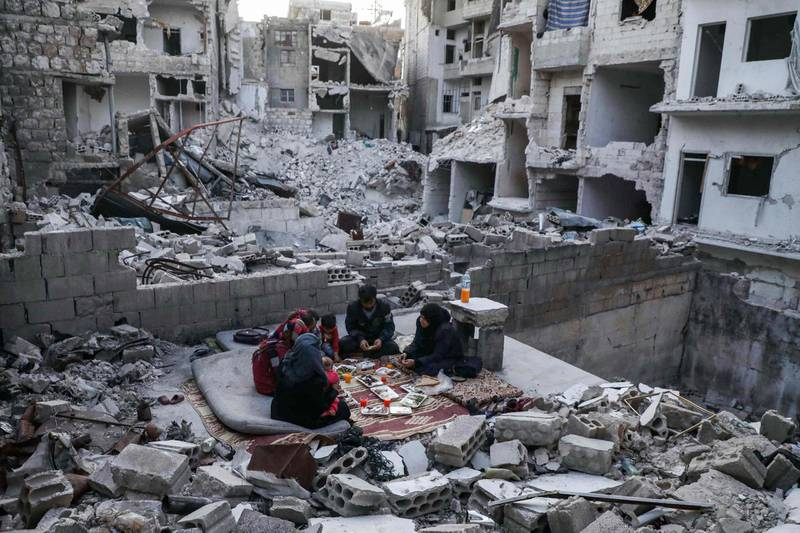 """This picture taken on May 4, 2020 during the Muslim holy fasting month of Ramadan shows members of the displaced Syrian family of Tariq Abu Ziad, from the town of Ariha in the southern countryside of the Idlib province, breaking their fast together for the sunset """"iftar"""" meal, in the midst of the rubble of their destroyed home upon their return to the town after fleeing during the previous military assault on the town by Syrian government forces and their allies.  / AFP / AAREF WATAD"""