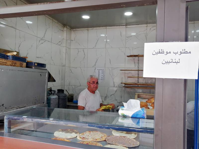 """Saeed Abdallah Mussa, 59, working at his bakery in Beirut adorned with a sign that reads """"we want Lebanese employees"""". Sunniva Rose / The National"""