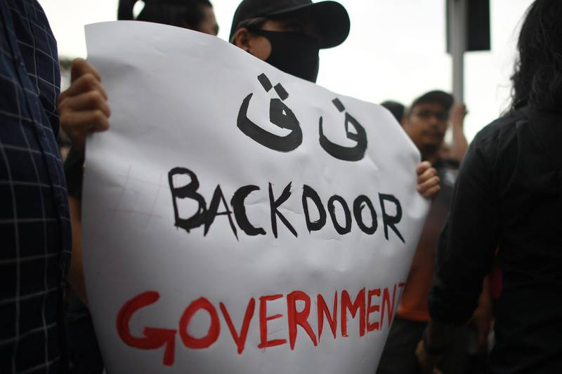A protester holds a sign while taking part in a demonstration to protest the ejection of the democractically elected government in Kuala Lumpur on March 1, 2020, after Muhyiddin Yassin was sworn in as prime minister following the reformist government's collapse. Muhyiddin, a staunch Muslim nationalist backed by a scandal-mired party, was sworn in as Malaysia's premier on March 1 after a reformist government's collapse, but ex-leader Mahathir Mohamad, 94, slammed the move as illegal. / AFP / Mohd RASFAN