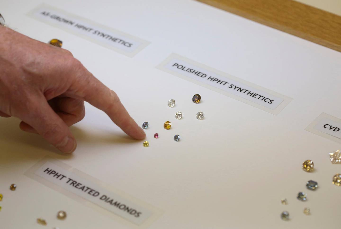 An employee points at polished high pressure high temperature (HPHT) synthetically produced diamonds at De Beers Technologies research laboratory in Maidenhead, U.K., on Tuesday, June 30, 2015. About 360,000 carats of man-made gems were produced last year, compared with 126 million carats of natural diamonds. Photographer: Chris Ratcliffe/Bloomberg