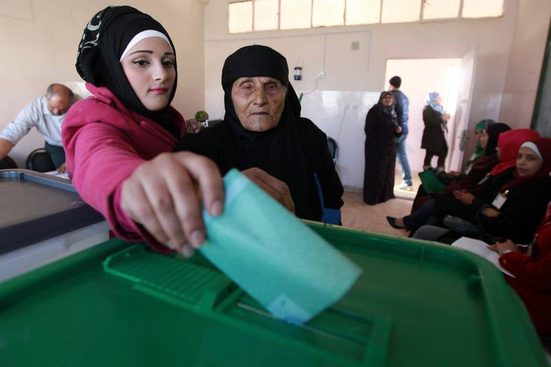 A woman helps her grandmother cast her ballot at a polling station in Amman January 23, 2013. Polling stations opened on Wednesday in Jordanian elections boycotted by the Muslim Brotherhood, which says the electoral system is rigged in favour of tribal areas and against the large urban centres. Eyewitnesses reported queues of about a dozen people apiece at several polling stations across the kingdom just before the polls opened at 7 a.m. (0400 GMT). REUTERS/Muhammad Hammad (JORDAN - Tags: POLITICS ELECTIONS) *** Local Caption ***  AMM56_JORDAN-ELECTI_0123_11.JPG