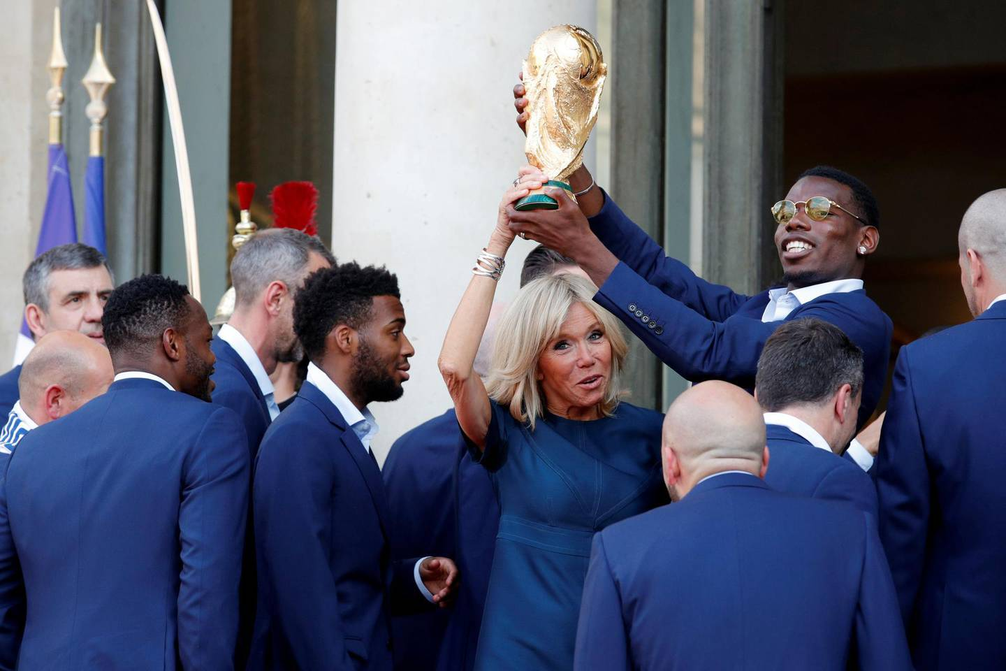 Brigitte Macron, the wife of French President Emmanuel Macron (not pictured), and player Paul Pogba hold the trophy before a reception to honour the France soccer team after their victory in the 2018 Russia Soccer World Cup, at the Elysee Palace in Paris, France, July 16, 2018.   REUTERS/Philippe Wojazer