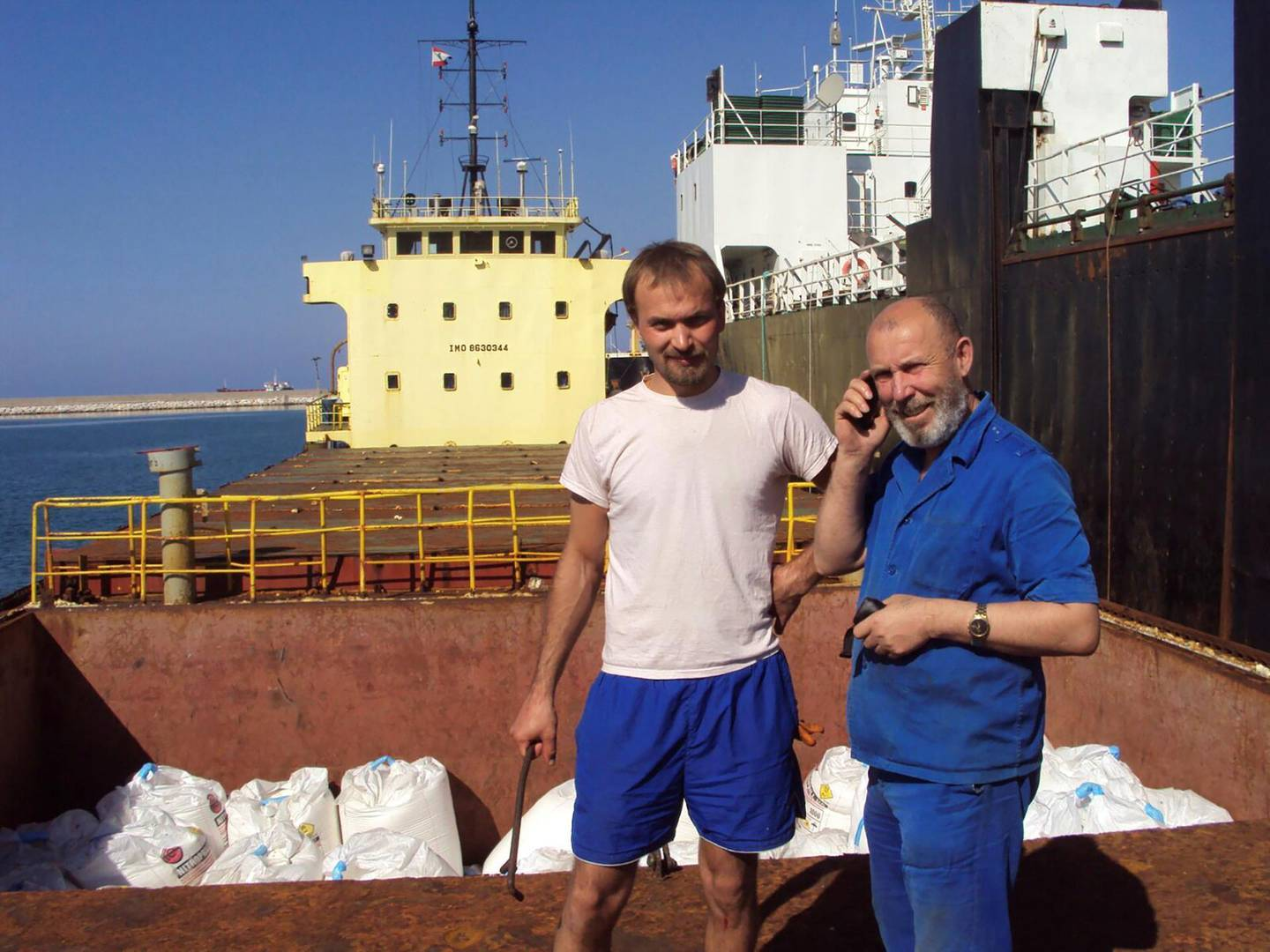 Boris Prokoshev (R), captain of cargo vessel Rhosus, and boatswain Boris Musinchak pose next to a freight hold loaded with ammonium nitrate in the port of Beirut, Lebanon, in a summer 2014 photograph. Picture taken in summer 2014. REUTERS/Personal archives of Boris Musinchak