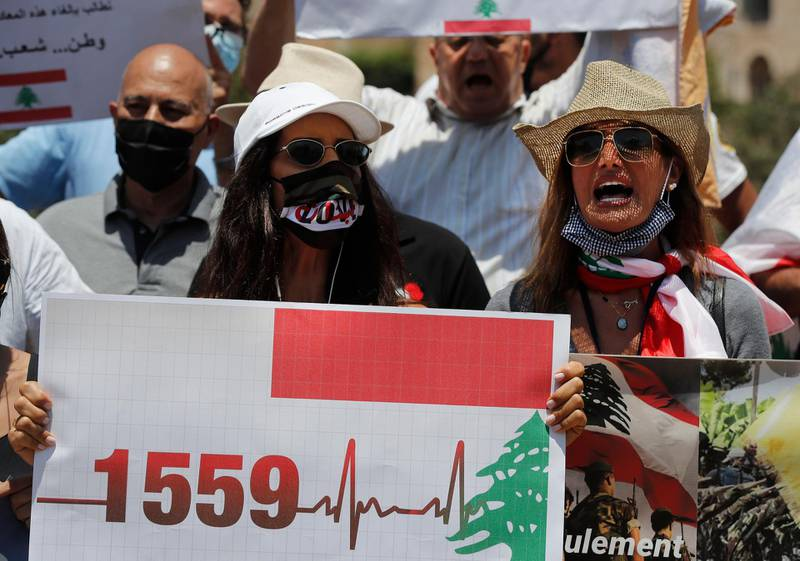 Anti-Hezbollah protesters shout slogans and hold a placard with the U.N. Resolution 1559, which was adopted in Sept., 2004, that called for disarmament all Lebanese and non-Lebanese militias, during a sit-in against Hezbollah and Iran in front the United Nations headquarters, in Beirut, Lebanon, Friday, July 24, 2020. (AP Photo/Hussein Malla)