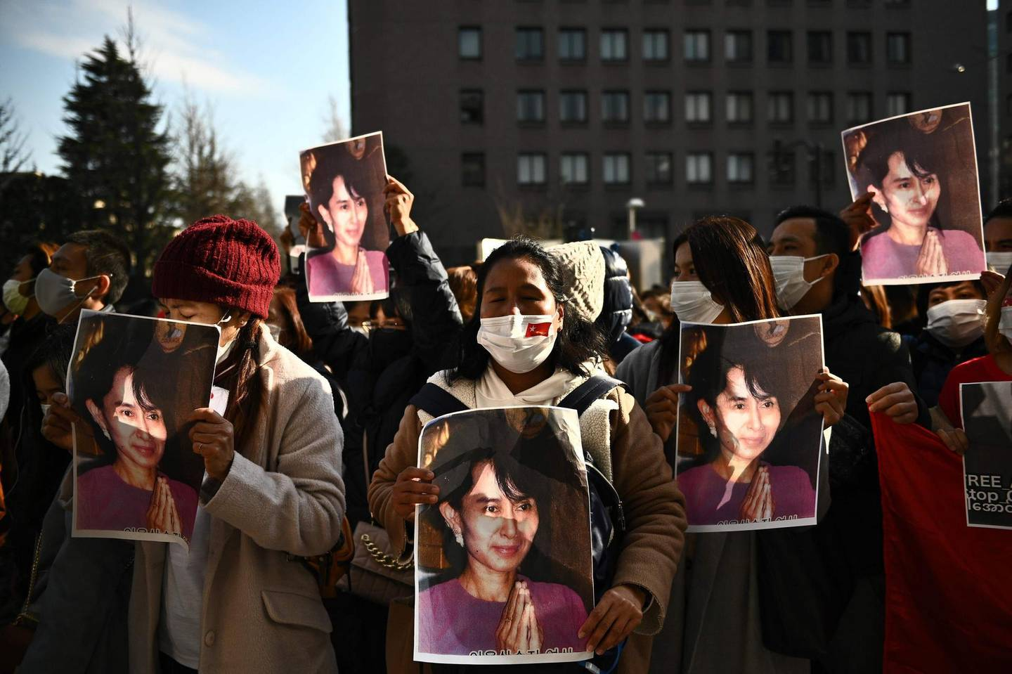 A group of Myanmar activists hold the portrait of Aung San Suu Kyi during a protest outside UN building in Tokyo on February 1, 2021 following a military coup in the country by a general after arresting civilian leader Aung San Suu Kyi and other senior officials. / AFP / Philip FONG
