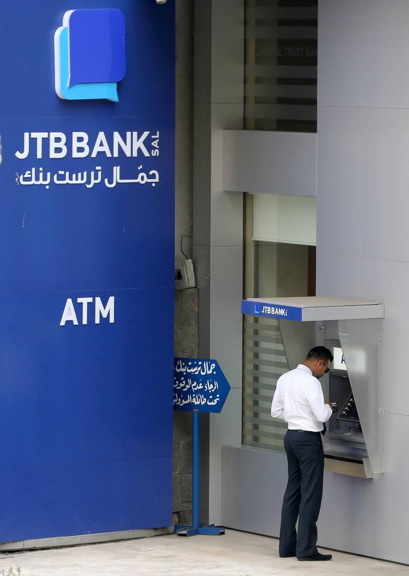 A man uses an ATM outside Jammal Trust Bank (JTB) branch in Ashrafieh, Lebanon, August 30, 2019. REUTERS/Mohamed Azakir