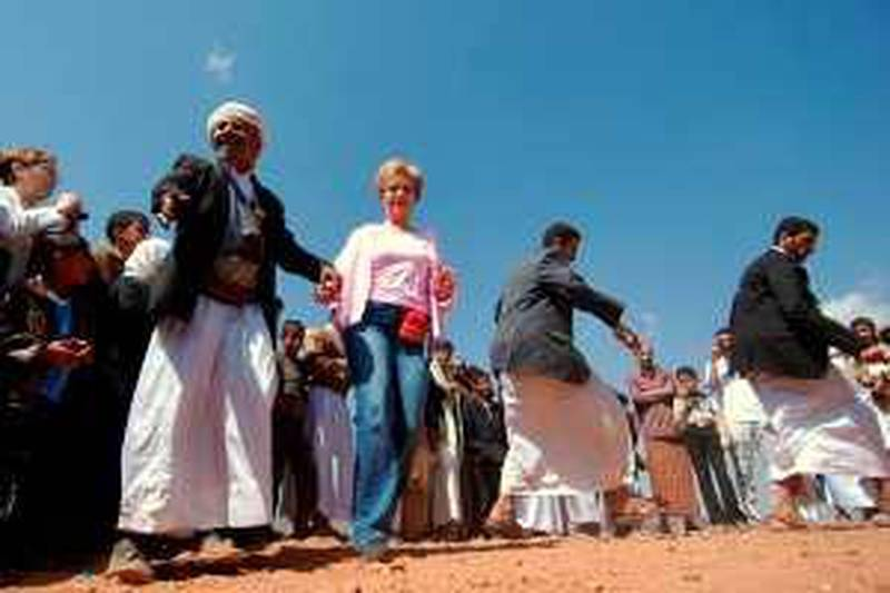 A foreign woman dances with Yemeni men at the touristic area of Wadi al-Daher, on the outskirts of Sanaa, on February 13, 2010. Calm prevailed in northern Yemen on the second day of a shaky truce between government forces and Shiite rebels that broke into deadly violence hours after it went into effect, both sides said.   AFP PHOTO/MOHAMED HUWAIS